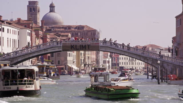 Slow motion shot of the packed Grand Canal with tourists crossing the Ponte Scalzi bridge