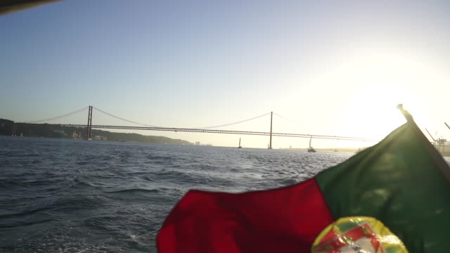 slow motion shot of the portuguese flag on the back of a boat - musical instrument bridge stock videos & royalty-free footage