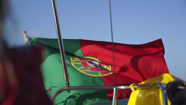 slow motion shot of the portuguese flag on the back of a boat - portugal stock videos & royalty-free footage