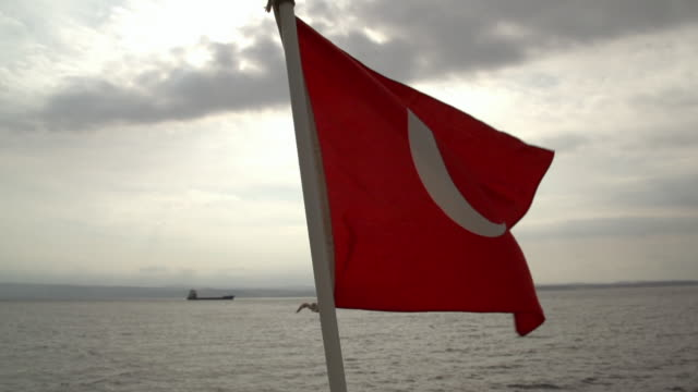 Slow motion shot of the Turkish flag flying from the stern of a boat.