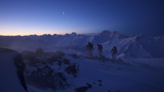 slow motion shot of three hikers walking up a mountain near mount elbrus at dawn - teamwork stock-videos und b-roll-filmmaterial