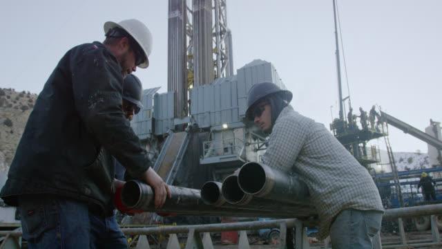 vídeos de stock, filmes e b-roll de tiro em câmera lenta de três trabalhadores do campo de petróleo removendo as tampas protetoras do fio do tubo de perfuração em um local de perfuração de óleo e gás em um dia ensolarado - oleoduto