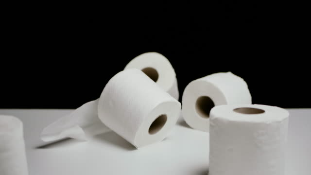 slow motion shot of tissue paper rolls falling down in black background copy space studio shot - tissue paper stock videos & royalty-free footage