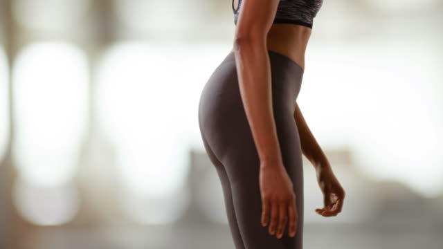 Slow motion shot of toned black female stretching leg muscles indoors
