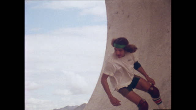 slow motion shot of tony alva, a professional skateboarder, skateboarding in a concrete pipe in the desert and placing a sticker on the concrete as a... - young men stock videos & royalty-free footage