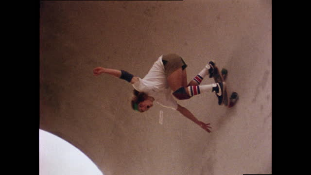 slow motion shot of tony alva, a professional skateboarder, skateboarding in a concrete pipe in the desert; 1978. - young men stock videos & royalty-free footage