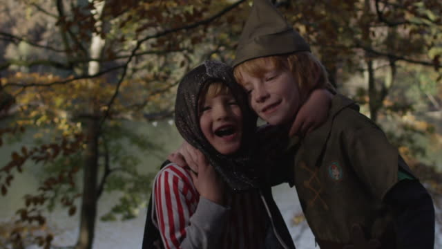 slow motion shot of two boys with their arms around each other laughing. they are framed by autumnul woodland and both wearing fancy dress. - 40 seconds or greater stock videos & royalty-free footage