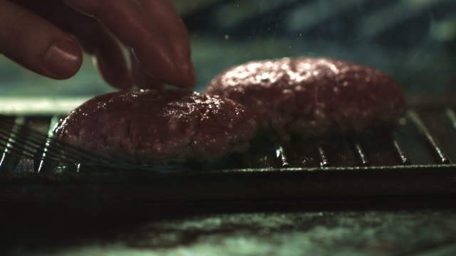 slow motion shot of two burgers cooking on a griddle. - グリルパン点の映像素材/bロール