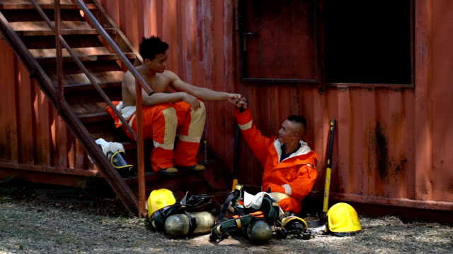 slow motion shot of two firefighters making a fist bump after mission success - retter rettungsaktion stock-videos und b-roll-filmmaterial