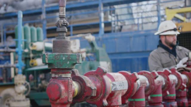 vídeos de stock, filmes e b-roll de tiro em câmera lenta de dois trabalhadores do campo petrolífero masculino bombeando linhas para baixo em um local de perfuração de óleo e gás em uma manhã fria e de inverno - boca de poço