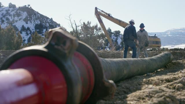 vídeos de stock, filmes e b-roll de tiro em câmera lenta de dois trabalhadores do campo petrolífero masculino apertando/soltando acoplamentos com um martelo para soprar linhas de bomba em um local de perfuração de óleo e gás em uma manhã ensolarada de inverno - boca de poço
