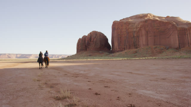 slow motion shot of two native american children (navajo) riding their horses in the monument valley desert of arizona/utah next to a large rock formation at sunset - all horse riding stock videos & royalty-free footage