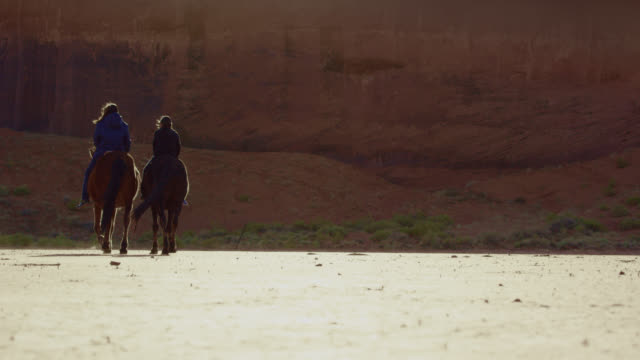 slow motion shot of two native american people riding horses across a flat plain in front of a large stone wall on a sunny day - recreational horse riding stock videos & royalty-free footage