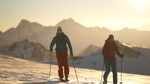vidéos et rushes de coup de ralenti de deux skieurs traversant un champ de neige avec le soleil derrière - sport d'hiver