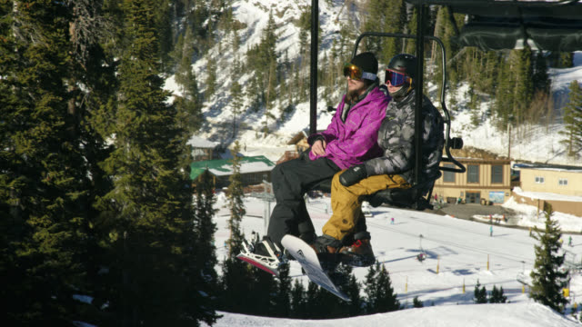 slow motion shot of two snowboarders in full winter gear riding the ski lift at eldora ski resort near boulder, colorado on a bright, sunny day in winter - ski holiday stock videos & royalty-free footage
