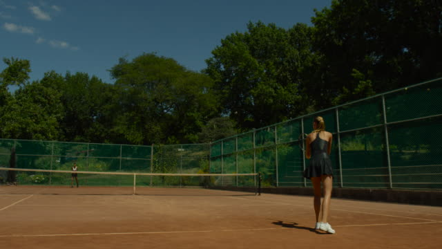Slow motion shot of two women playing tennis on clay court surrounded by trees