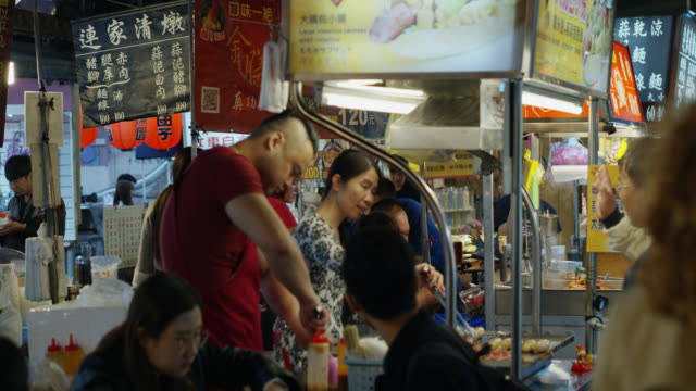 slow motion shot of vendors at raohe night market, taipei - insel taiwan stock-videos und b-roll-filmmaterial