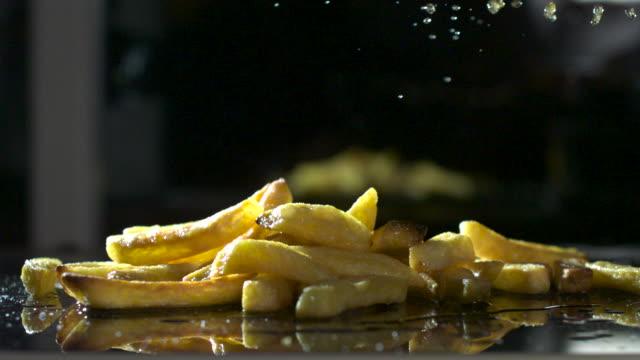 Slow motion shot of vinegar being sprinkled over a pile of chips.