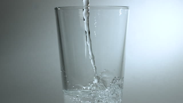 vídeos de stock, filmes e b-roll de slow motion shot of water being poured into a glass. - copo