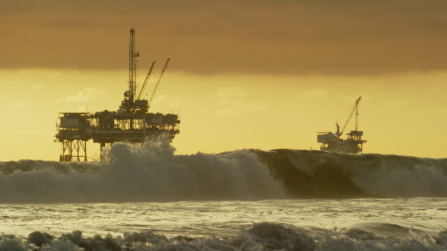 stockvideo's en b-roll-footage met slow motion shot of waves crashing onto the shores of huntington beach in southern california with several offshore oil drilling rig platforms and an oil (petroleum) tanker on the horizon in the distance at sunset under a dramatic, stormy sky - offshore