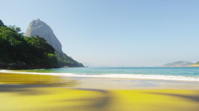 vídeos de stock, filmes e b-roll de slow motion shot of waves on red beach in rio. - 2013