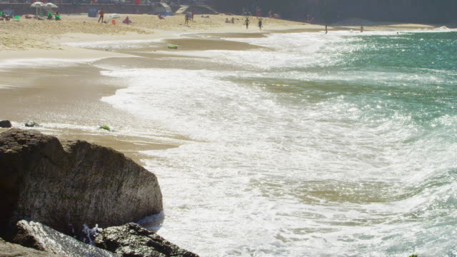 vídeos y material grabado en eventos de stock de slow motion shot of waves washing up on red beach in rio. - 2013