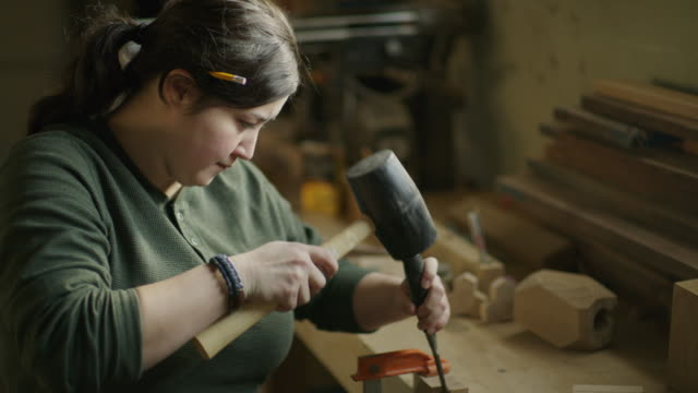 vídeos de stock e filmes b-roll de slow motion shot of woman chiseling wood in workshop / provo, utah, united states - provo