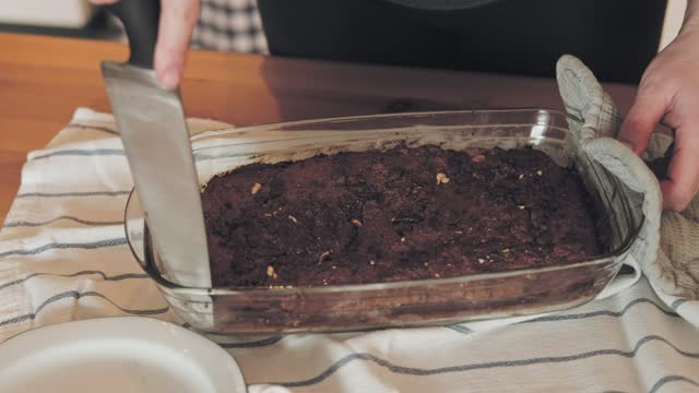 slow motion shot of woman cutting chocolate cake in baking tray - baking tray stock videos & royalty-free footage