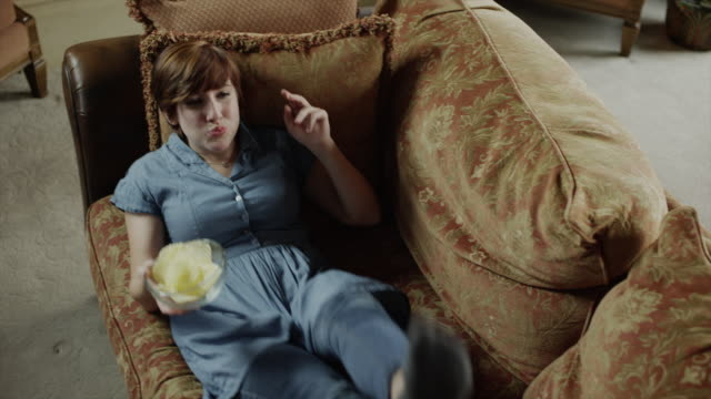 vídeos de stock e filmes b-roll de slow motion shot of woman falling on sofa eating potato chips / cedar hills, utah, united states,  - lanche