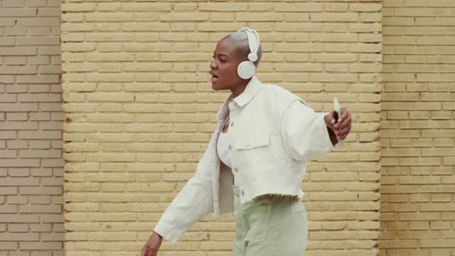 slow motion shot of woman listening to music and dancing - mobilität stock-videos und b-roll-filmmaterial