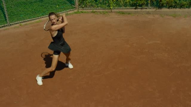 slow motion shot of woman making forehand return of tennis ball on clay court - スポーツ競技点の映像素材/bロール