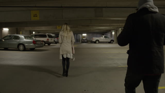 slow motion shot of woman pointing gun at man following her in parking garage / provo, utah, united states - provo stock videos & royalty-free footage