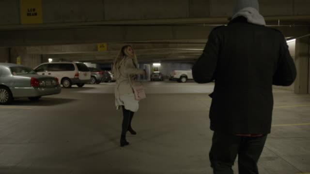 Slow motion shot of woman pointing gun at man following her in parking garage / Provo, Utah, United States