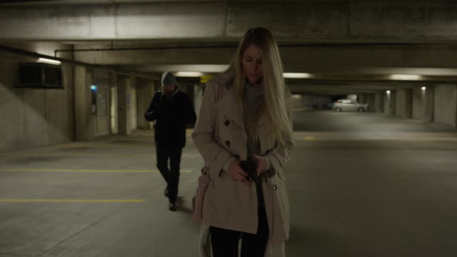 slow motion shot of woman pointing gun at man following her in parking garage / provo, utah, united states - provo stock videos & royalty-free footage
