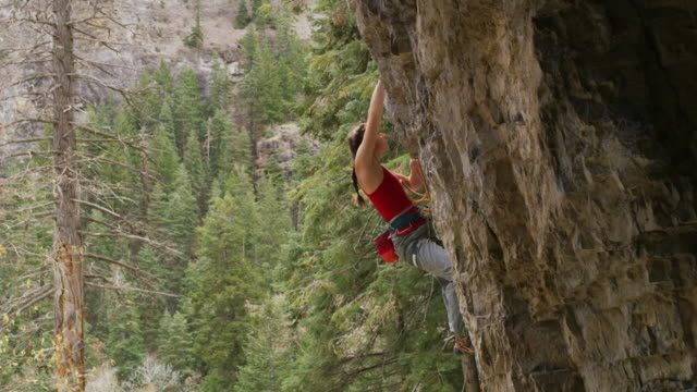 slow motion shot of woman rock climbing / american fork canyon, utah, united states - corda video stock e b–roll