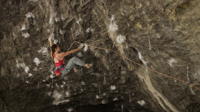 slow motion shot of woman rock climbing in cave / american fork canyon, utah, united states - braided hair stock videos and b-roll footage