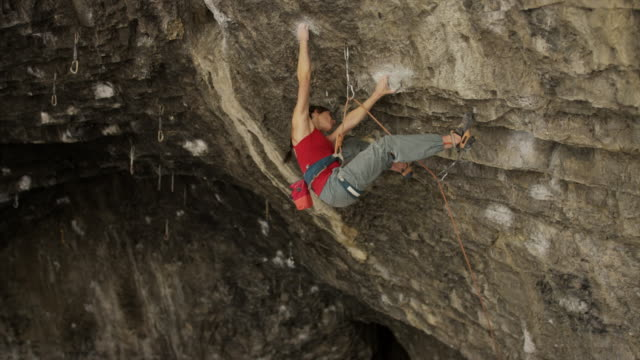 slow motion shot of woman rock climbing in cave and falling / american fork canyon, utah, united states - braided hair stock videos & royalty-free footage