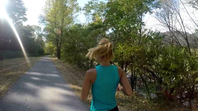 vidéos et rushes de le mouvement lent coup de femme en cours d'exécution - joggeuse