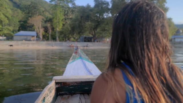 vidéos et rushes de slow motion shot of woman sitting in boat moving towards shore against trees, she is with brown hair - lombok, bali - brown hair