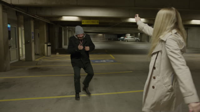 slow motion shot of woman spraying mace at face of man following her in parking garage / provo, utah, united states - provo stock videos & royalty-free footage