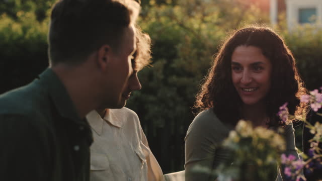 Slow motion shot of woman talking to male friends while sitting at garden party