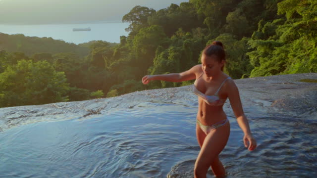 slow motion shot of woman wearing bikini walking in flowing river at forest, portrait of female during sunny day - ilhabela, brazil - dekolleté stock-videos und b-roll-filmmaterial