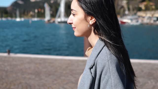 vídeos y material grabado en eventos de stock de slow motion shot of woman with nose piercing walking at harbour - sólo mujeres jóvenes