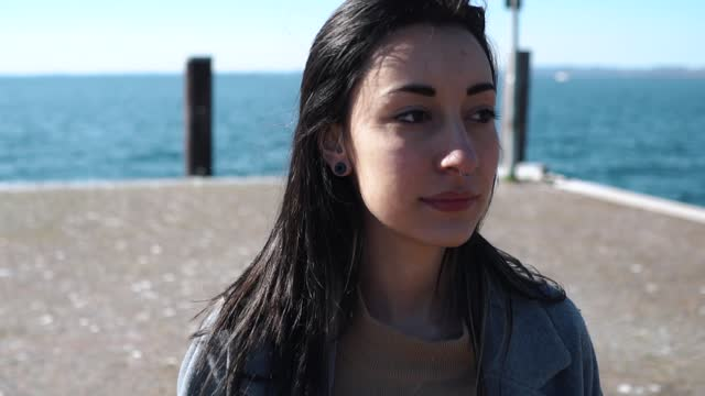 slow motion shot of woman with nose piercing walking at seafront - nose piercing stock videos & royalty-free footage