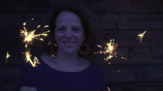 slow motion shot of woman with sparklers - one mid adult woman only stock videos & royalty-free footage