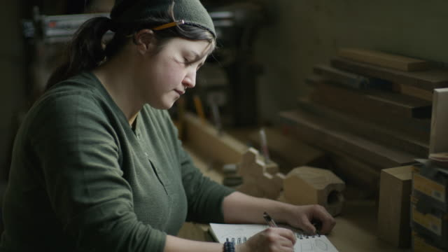vidéos et rushes de slow motion shot of woman writing in notebook with pen in workshop / provo, utah, united states - provo