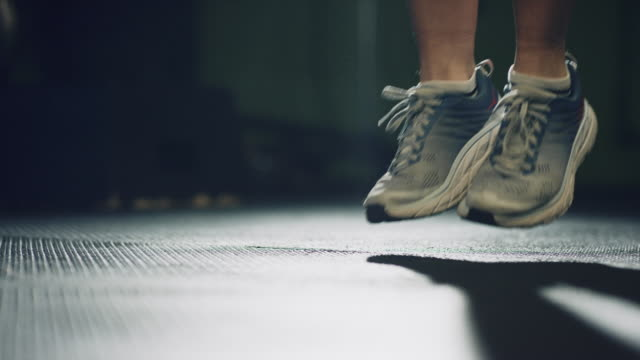 slow motion shot of woman's feet wearing athletic shoes jumping rope in an indoor gym - skipping stock videos & royalty-free footage