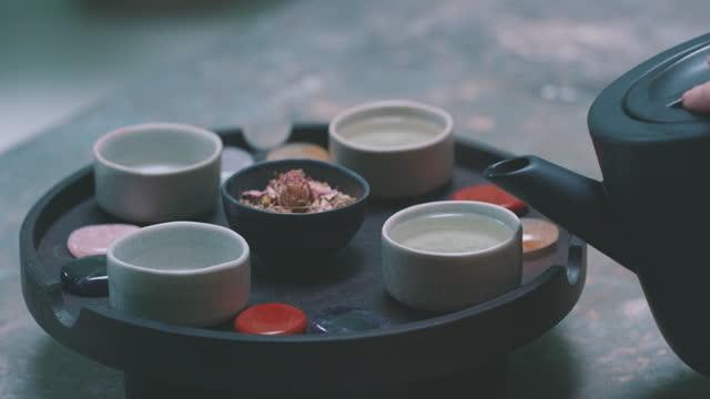 vidéos et rushes de slow motion shot of woman's hand pouring fresh tea - une seule femme d'âge moyen