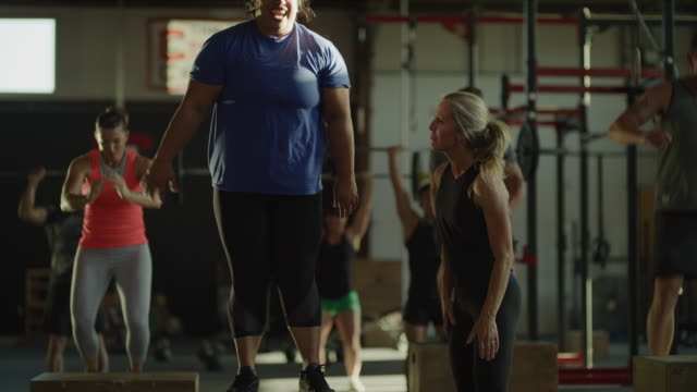 Slow motion shot of women celebrating successful box jump in gymnasium / Lehi, Utah, United States