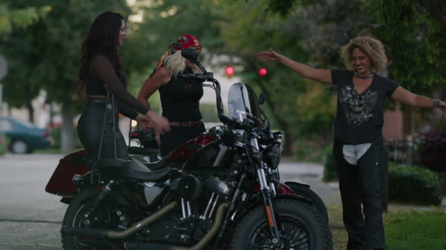 Slow motion shot of women chest bumping near motorcycles / Payson, Utah, United States